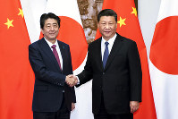 In this photo released by Xinhua News Agency, Japanese Prime Minister Shinzo Abe, left, shakes hands with Chinese President Xi Jinping as they pose for photographers before a meeting at the Diaoyutai State Guesthouse in Beijing, Friday, Oct. 26, 2018. (Li Tao/Xinhua via AP)