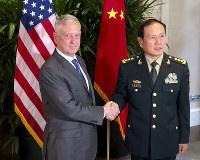 In this Oct. 18, 2018 photo, U.S. Defense Secretary Jim Mattis, left, meets Chinese Defense Minister Wei Fenghe in Singapore. (AP Photo/Robert Burns)