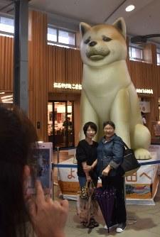 JR秋田駅に登場した秋田犬の巨大バルーンを背景に、記念撮影する人たち=秋田市のJR秋田駅で2018年9月7日午後1時30分、高野裕士撮影