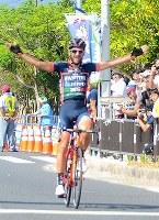 トップでゴールし、両手を広げ優勝を喜ぶアラン・マランゴーニ=名護市の21世紀の森屋内運動場前で2018年11月11日、琉球新報