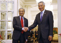 Malaysia's Prime Minister Mahathir Mohamad, left, shakes hands with Singapore's Prime Minister Lee Hsien Loong at the Istana in Singapore, on Nov. 12, 2018. (Feline Lim/Pool Photo via AP)