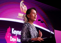 Myanmar's leader Aung San Suu Kyi delivers the keynote speech at the ASEAN Business and Investment Summit 2018, a parallel summit in the ongoing ASEAN Summit 2018 in Singapore, on Nov. 12, 2018. (AP Photo/Bullit Marquez)
