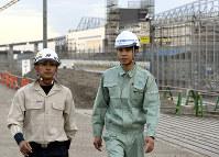 「海の森水上競技場」の建設現場(奥)で働くフィリピン出身のマークさん(左)とベトナム出身のディンさん=東京都臨海部で、丸山博撮影