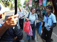 観客の女性(中央)を競技会場への移動用カートに笑顔で案内する大会ボランティア(右)