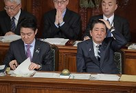 Prime Minister Shinzo Abe, right, and Justice Minister Takashi Yamashita listen to a question about a bill aimed at expanding the acceptance of foreign workers during a House of Representatives plenary session on Nov. 13, 2018. (Mainichi/Masahiro Kawata)