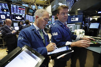 In this Nov. 7, 2018 file photo, trader Timothy Nick, center, works with specialist Michael O'Mara on the floor of the New York Stock Exchange. (AP Photo/Richard Drew)