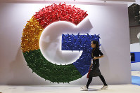 In this Nov. 5, 2018 photo, a woman carries a fire extinguisher past the logo for Google at the China International Import Expo in Shanghai. (AP Photo/Ng Han Guan)