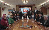 In this Nov. 12, 2018 photo, Turkish President Recep Tayyip Erdogan poses for photos with Turkish journalists aboard his plane. (Presidential Press Service via AP, Pool)