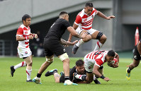 Japan's William Tupou is tackled by New Zealand's Angus Ta'avao during their rugby test at the Ajinomoto Stadium in Tokyo, on Nov. 3, 2018. (AP Photo/Eugene Hoshiko)
