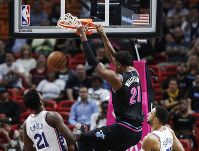 Miami Heat center Hassan Whiteside dunks the ball against Philadelphia 76ers' center Joel Embiid in the first quarter of an NBA basketball game on Nov. 12, 2018, in Miami. (AP Photo/Brynn Anderson)