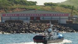日露間で北方領土の帰属確認の協議が進まない中、現地ではインフラ整備が進む。択捉島の工場には「択捉にようこそ」との看板が掲げられていた=択捉島で2014年6月、大前仁撮影