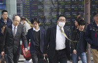 People walk by an electronic stock board of a securities firm in Tokyo, on Nov. 14, 2018. (AP Photo/Koji Sasahara)