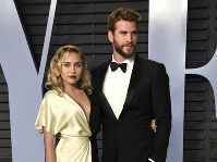 In this March 4, 2018 file photo, Miley Cyrus, left, and Liam Hemsworth arrive at the Vanity Fair Oscar Party in Beverly Hills, Calif. (Photo by Evan Agostini/Invision/AP)