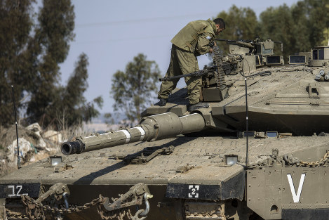 An Israeli soldier stands on a tank near the Israel Gaza border, on Nov. 13, 2018. (AP Photo/Tsafrir Abayov)