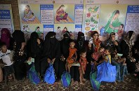 In this Aug. 24, 2018 photo, Rohingya refugees wait at a U.N. World Food Programme (WFP) facility to receive food supplements for their children in Kutupalong refugee camp, Bangladesh. (AP Photo/Altaf Qadri)