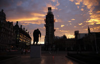 The sun rises as seen in Parliament Square with the statue of former Prime Minister Winston Churchill in the foreground in London, on Nov. 14, 2018. (AP Photo/Matt Dunham)