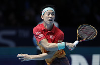 Kei Nishikori of Japan plays a return to Kevin Anderson of South Africa during their ATP World Tour Finals tennis match at the O2 arena in London, on Nov. 13, 2018. (AP Photo/Alastair Grant)