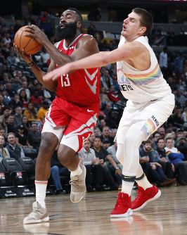Houston Rockets guard James Harden, left, drives the lane past Denver Nuggets center Nikola Jokic in the first half of an NBA basketball game on Nov. 13, 2018, in Denver. (AP Photo/David Zalubowski)