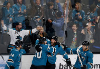 San Jose Sharks' Marc-Edouard Vlasic (44) and Marcus Sorensen (20) celebrate with teammate Joe Thornton, third from left, who scored his 400th career goal in the third period of an NHL hockey game against the Nashville Predators, in San Jose, California, on Nov. 13, 2018. (AP Photo/Josie Lepe)