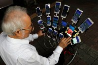 11月13日、台湾の新北市で、自転車に15台ものスマホを取り付けてゲーム「ポケモンGO」を楽しむ70歳の男性が話題となっている。写真は12日撮影(2018年 ロイター/Tyrone Siu)