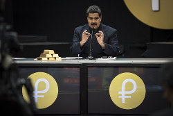 仮想通貨「ペトロ」について記者会見するベネズエラのマドゥロ大統領。横に積んであるのは金の延べ棒(2018年3月、Bloomberg)