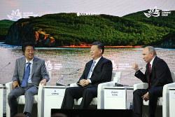 今年9月にロシア・ウラジオストクで開かれた東方経済フォーラムで並んだ日中露首脳。左から安倍晋三首相、習近平国家主席、ウラジーミル・プーチン大統領(Bloomberg)