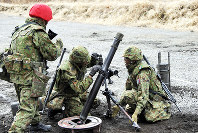 In this photo provided by the Ground Self-Defense Force, GSDF personnel operate an 81-millimeter mortar.