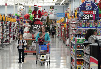 In this Nov. 9, 2018, file photo shoppers walks down an isle at a Walmart Supercenter in Houston.  (AP Photo/David J. Phillip)