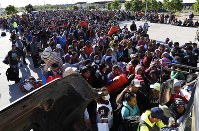 Migrants traveling with a caravan hoping to reach the U.S. border, wait in line to board buses in La Concha, Mexico, on Nov. 14, 2018. (AP Photo/Marco Ugarte)