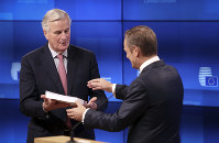 EU chief Brexit negotiator Michel Barnier, left, delivers the draft withdrawal agreement to European Council President Donald Tusk during a media conference at the Europa building in Brussels, on Nov. 15, 2018. (AP Photo/Francisco Seco)
