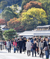 京都・嵐山の渡月橋を歩く大勢の観光客ら=京都市右京区で2018年11月16日午前10時39分、川平愛撮影
