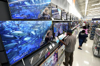 In this Nov. 9, 2018, file photo shoppers look at televisions at a Walmart Supercenter in Houston. (AP Photo/David J. Phillip)