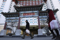 Residents pass by The Peninsula hotel which announced that it was investigating claims in an online video that supposedly showed the hotel cleaners using dirty towels to wipe cups and sinks, in Beijing, on Nov. 16, 2018. (AP Photo/Ng Han Guan)