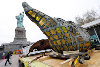 The original torch of the Statue of Liberty rests on a hydraulically stabilized transporter, on Nov. 15, 2018 in New York. (AP Photo/Richard Drew)