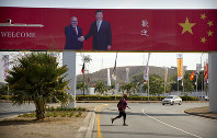 In this Nov. 15, 2018 photo, a woman crosses the street near a billboard commemorating the state visit of Chinese President Xi Jinping in Port Moresby, Papua New Guinea. (AP Photo/Mark Schiefelbein)