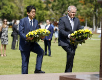 Japanese Prime Minister Shinzo Abe, left, lays a wreath along with Australian Prime Minister Scott Morrison at the Cenotaph War Memorial in Darwin, Australia, on Nov. 16, 2018. (Glenn Campbell/Pool Photo via AP)