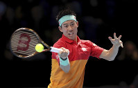 Japan's Kei Nishikori returns a shot to Austria's Dominic Thiem, during the ATP World Tour Finals men's singles tennis match at the O2 arena in London, on Nov. 15, 2018. (John Walton/PA via AP)