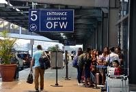 マニラ国際空港にある出稼ぎ労働者用のターミナル入り口に並ぶフィリピン人=武内彩撮影