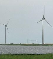 太陽光発電のパネルと風力発電の発電機が一望できる=福島県南相馬市で今年6月、鎌田さん提供