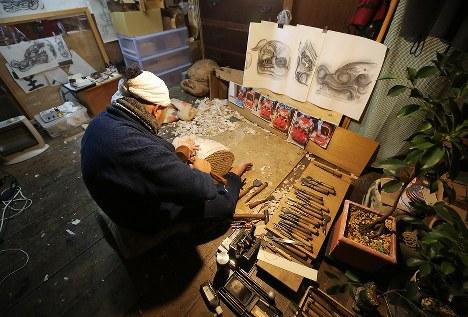 図案や写真を見ながら三字の神楽の獅子頭を彫る橋本和成さん。「起伏が多くて表面積が大きく、複雑な部類に入る」という=福島県二本松市で2017年12月24日、喜屋武真之介撮影