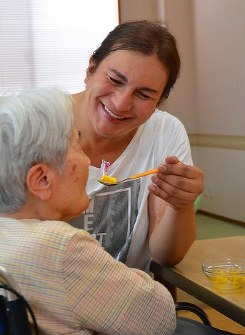 In this file photo, Reia Zafra, from the Philippines, serves a spoonful of sweet jelly to a woman with dementia at a care home in Tatebayashi, Gunma Prefecture, on July 3, 2018. (Mainichi)