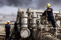 In this Dec. 13, 2009 file photo, Iraqi laborers work at the Rumaila oil refinery in Zubair near the city of Basra, Iraq. (AP Photo/Nabil al-Jurani)