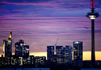 An aircraft flies over the bank buildings and the television tower before sunrise in Frankfurt, Germany, on Nov. 12, 2018. (AP Photo/Michael Probst)