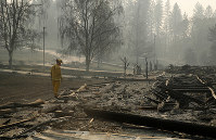 A firefighter searches for human remains in a trailer park destroyed in the Camp Fire, on Nov. 16, 2018, in Paradise, Calif. (AP Photo/John Locher)