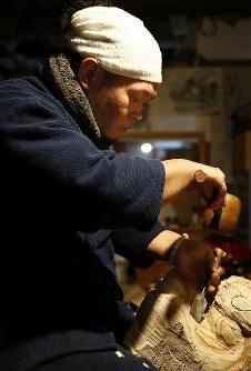 下書きや写真を見ながら獅子頭を彫る和成さん=福島県二本松市で2017年12月24日、喜屋武真之介撮影