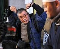 獅子頭の耳の動きを説明する三字芸能保存会の岩川会長(左)=福島県二本松市で2017年12月24日、喜屋武真之介撮影