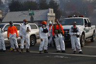 First responders watch as the motorcade of President Donald Trump visits a neighborhood impacted by the wildfires, on Nov. 17, 2018, in Paradise, Calif. (AP Photo/Evan Vucci)