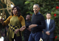 In this Oct. 31, 2016 file photo, President Barack Obama and the first lady Michelle Obama dance with kids to the beat of
