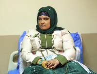 In this Monday, Nov. 5, 2018 photo, Saja Ahmed Saleem, 17, who was injured in an explosion in 2007, holding her artificial hand before her reconstructive surgery in Baghdad, Iraq. (AP Photo/Hadi Mizban)