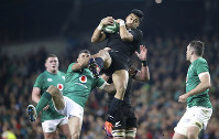 New Zealand's Rieko Ioane is pulled down by Ireland's Rob Kearney during the rugby union international match between Ireland and the New Zealand All Blacks at the Aviva Stadium, Dublin, Ireland, on Nov. 17, 2018. (Niall Carson, PA via AP)